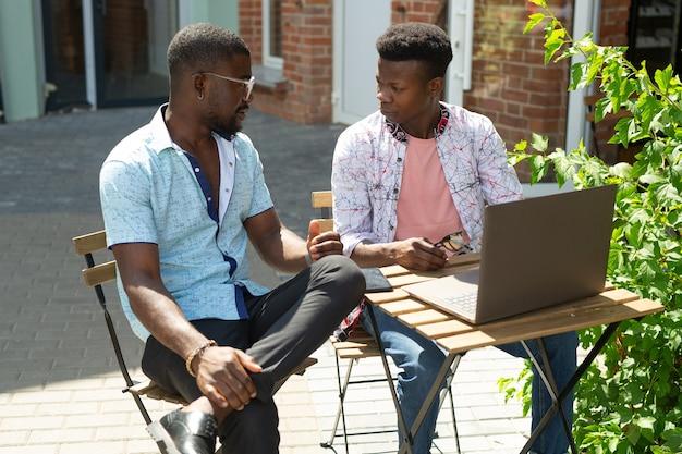 Dois homens africanos na mesa com laptop