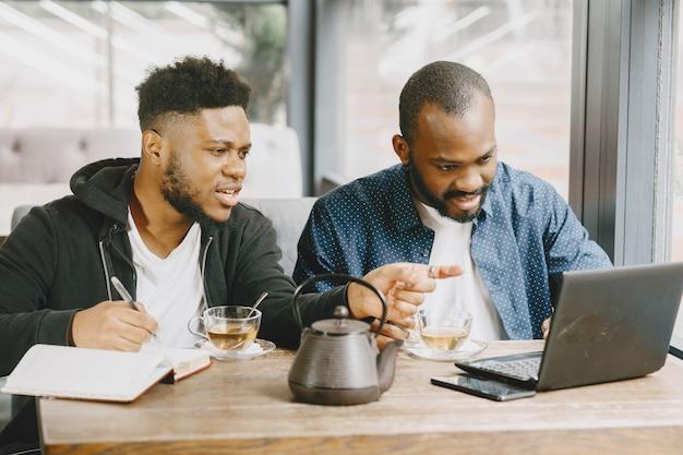 Dois homens afro-americanos trabalhando atrás de um laptop e escrevendo em um caderno. homens com barba, sentados em um café.