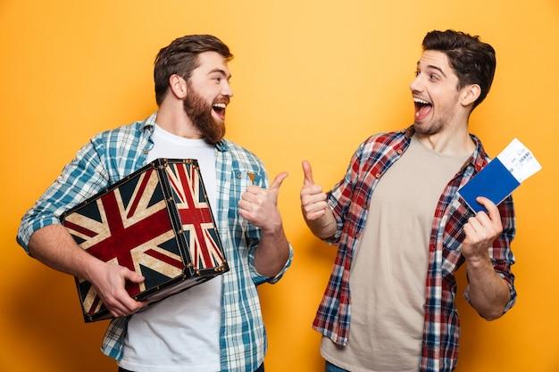 Dois homens alegres em camisas, preparando-se para tropeçar e mostrando os polegares enquanto olham um para o outro e segurando pasport com mala sobre parede amarela