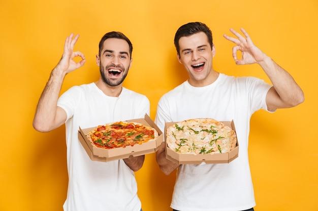Dois homens alegres, solteiros de 30 anos, em camisetas brancas, sorrindo e segurando caixas de pizza, isolados na parede amarela