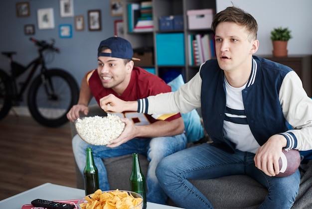 Dois homens animados na sala de estar