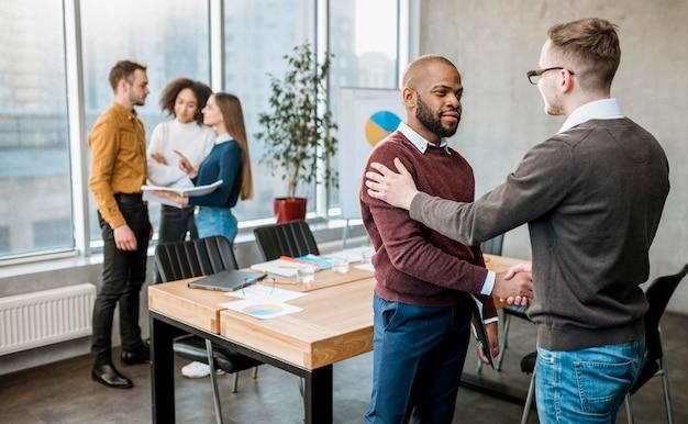 Dois homens apertando a mão em acordo após uma reunião