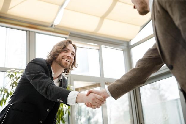 Dois homens apertando as mãos e olhando um para o outro
