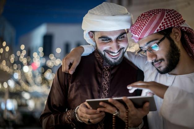 Dois homens árabes com tablet na cidade à noite