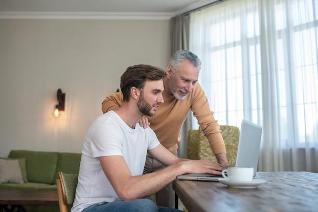 Dois homens assistindo algo em um laptop e parecendo envolvidos