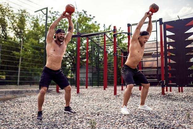 Dois homens atléticos malhando com um kettlebell no quintal de ginásio de rua.