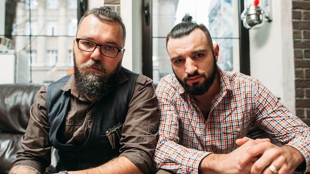 Dois homens barbudos com hobbies diferentes, mas estilo semelhante