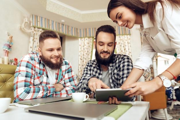 Dois homens barbudos estão sentados em um café com laptops