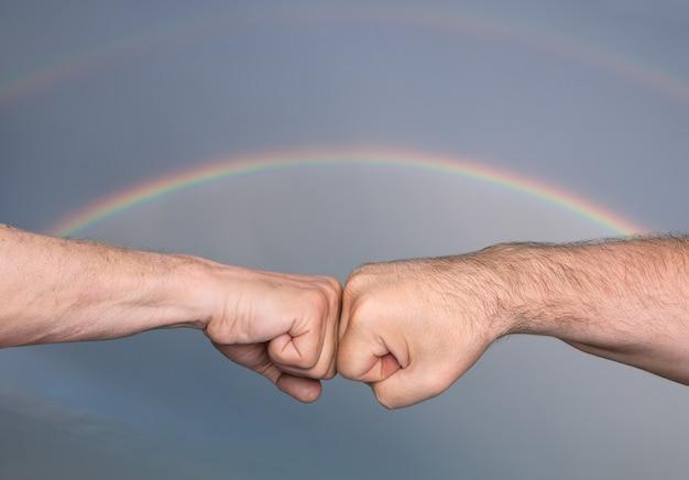 Dois homens batendo os punhos contra o fundo de um céu tempestuoso com arco-íris