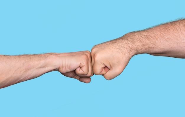 Dois homens batendo os punhos isolados em fundo azul