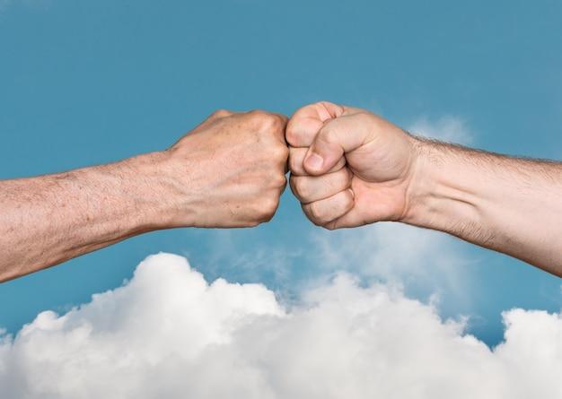 Dois homens batendo os punhos no céu azul com nuvens brancas