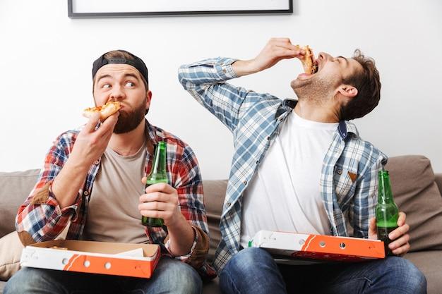 Dois homens bonitos em camisas casuais comendo pizza e bebendo cerveja, enquanto assistem a uma partida de futebol no apartamento