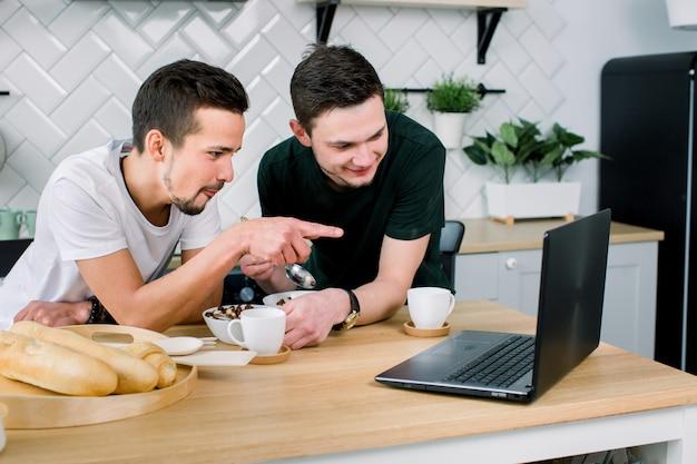 Dois homens bonitos jovens tomando café e tomando café enquanto estiver usando o laptop na cozinha, de manhã. sorrindo homens assistindo filme usando laptop e tomando café da manhã