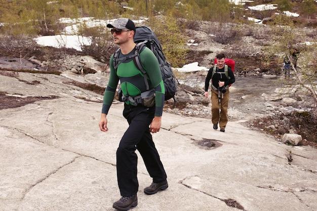 Dois homens caminham sobre as rochas nas montanhas