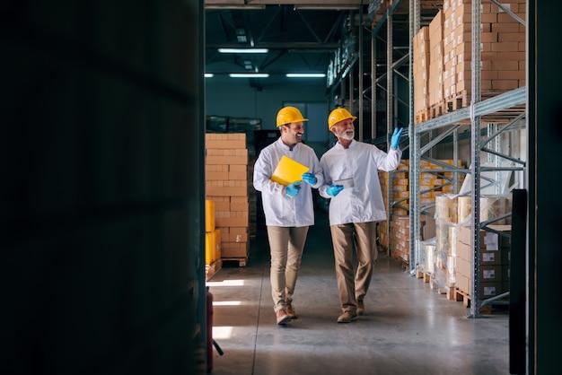 Dois homens caminhando no depósito. sênior segurando o tablet e uma pasta mais jovem.