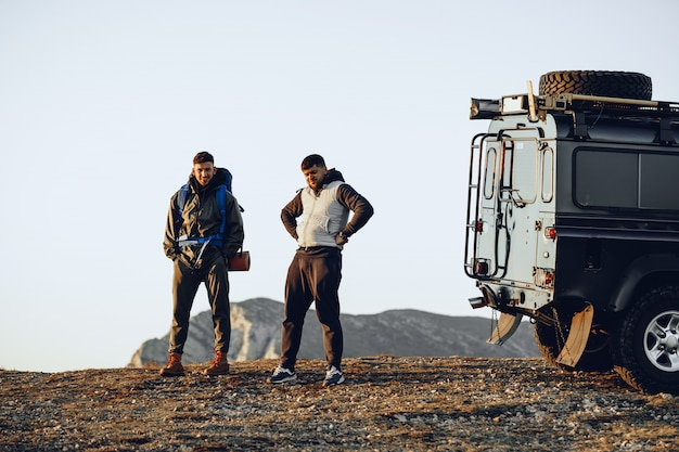 Dois homens caminhantes parados perto de um carro off-road se preparando para iniciar sua jornada