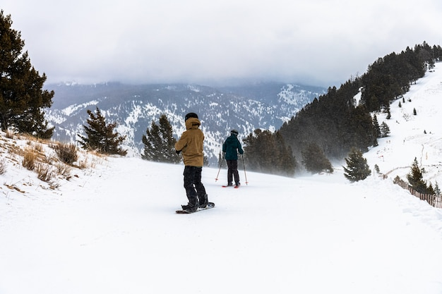 Dois homens cavalgando na neve do topo da montanha, jackson hole, wyoming, eua. clima de inverno com neve forte