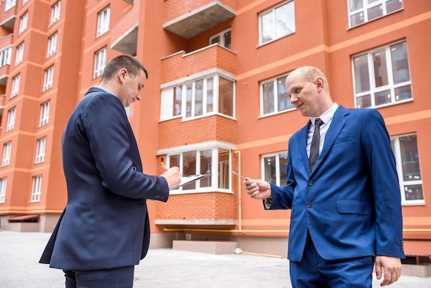 Dois homens com prancheta e chave perto do novo prédio
