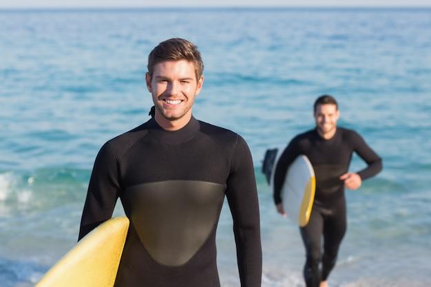 Dois homens com roupa de mergulho com prancha em um dia ensolarado