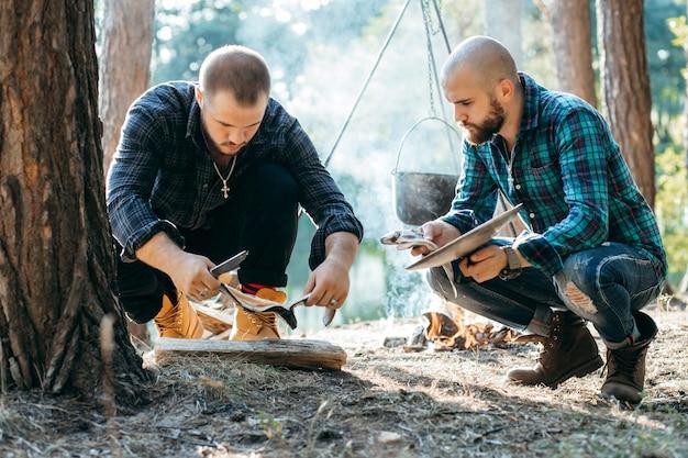 Dois homens com uma faca cortam peixes na floresta