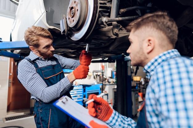 Dois homens consertando a suspensão no carro.