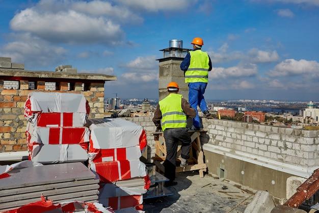 Dois homens, construtores profissionais em trajes de trabalho e capacetes laranja estão trabalhando com um sistema de ventilação no telhado de um prédio em construção