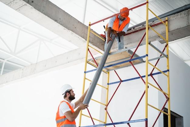 Dois homens construtores uniformizados arrastam o cano em um andaime no canteiro de obras