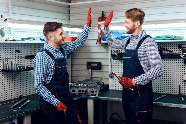 Dois homens dão cinco mais um para o outro por um bom trabalho.