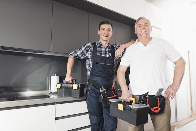 Dois homens de encanador estão na cozinha.