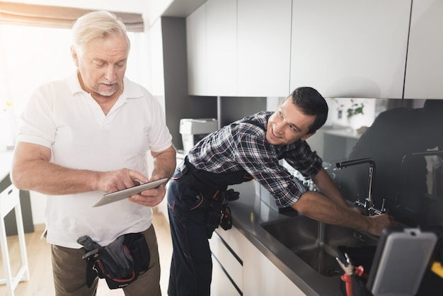 Dois homens de encanadores estão de pé na cozinha