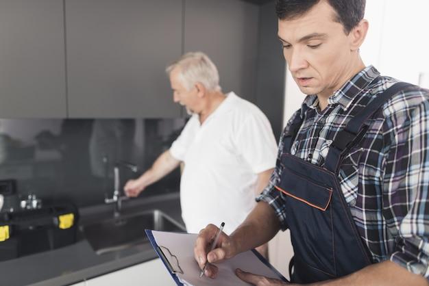 Dois homens de encanadores estão em pé na cozinha.