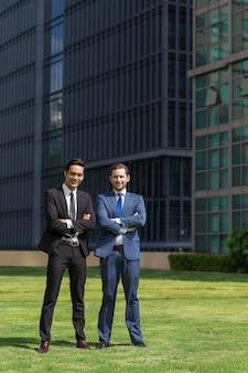 Dois homens de negócios adultos sorridentes de pé ao ar livre