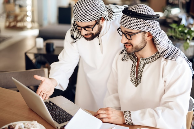 Dois homens de negócios árabes no portátil na tabela na sala de hotel.