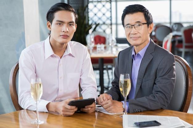 Dois homens de negócios asiáticos com taças de champanhe