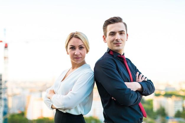 Dois homens de negócios, bom homem morena e mulher loira atraente ficar no telhado de costas
