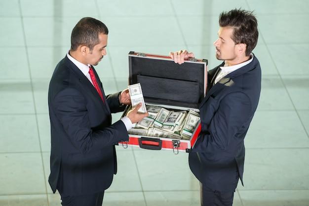 Dois homens de negócios com mala de metal cheia de dinheiro.