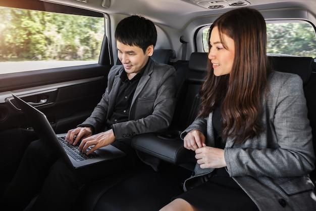 Dois homens de negócios e uma mulher trabalhando com um laptop enquanto estão sentados no banco de trás de um carro