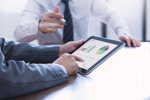 Dois homens de negócios em uma sala de reuniões discutem sobre desempenho financeiro e análise de investimentos com planilhas e gráficos na tela do tablet.