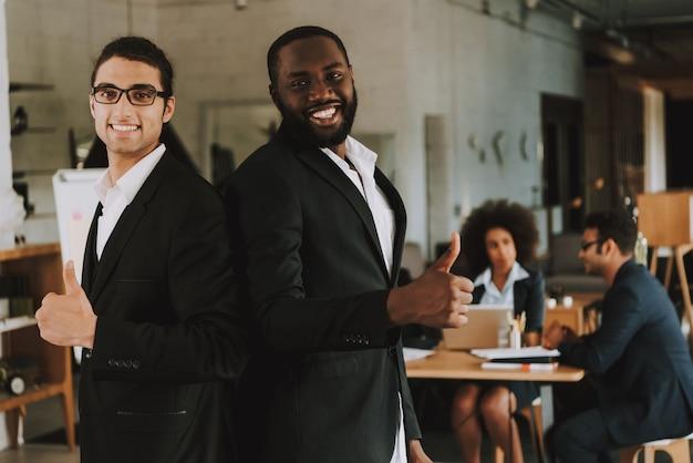 Dois homens de negócios está mostrando polegares para cima e sorrindo