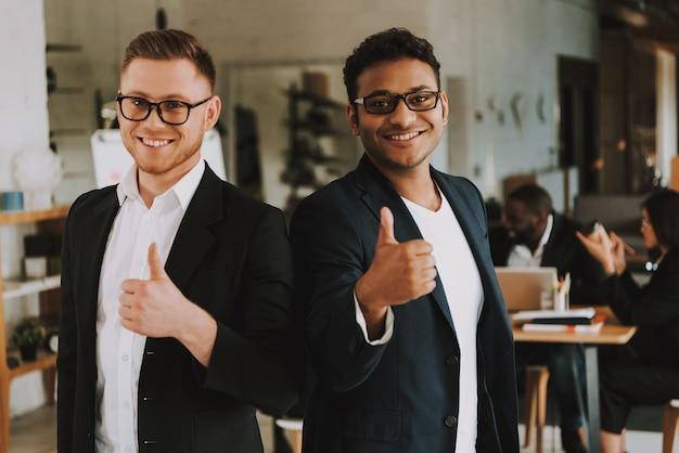 Dois homens de negócios estão mostrando os polegares acima e sorrindo.