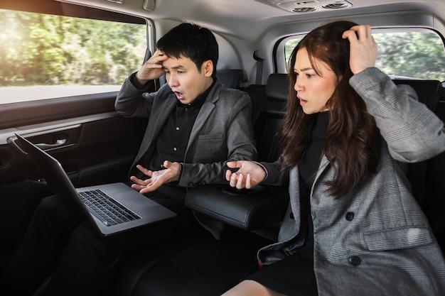 Dois homens de negócios estressados e uma mulher trabalhando com um laptop enquanto estão sentados no banco de trás de um carro