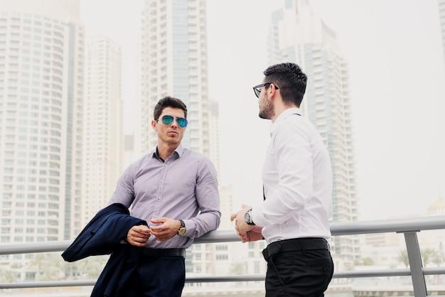 Dois homens de negócios modernos novos no fuzileiro naval de dubai inclinaram-se na cerca. de pé e discutindo sobre negócios.