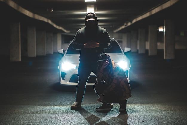 Dois homens de pé e agachado na frente do carro