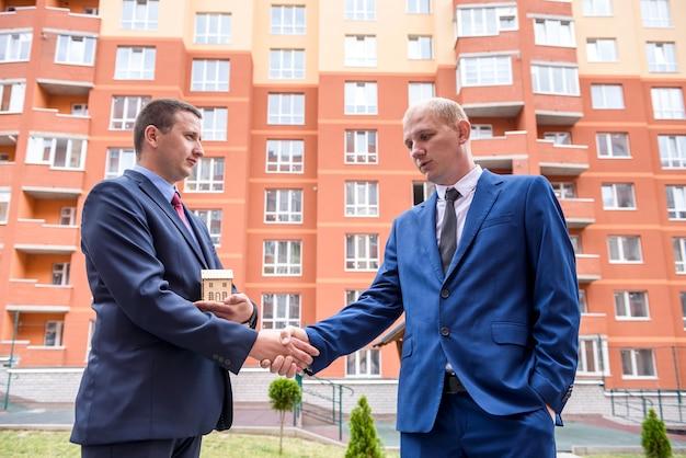 Dois homens de terno com prancheta e chaves negociam