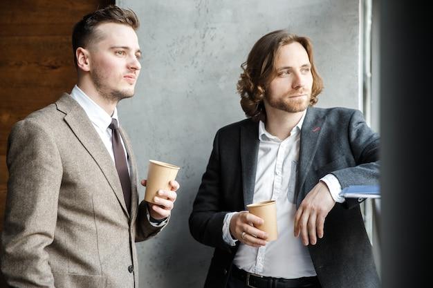 Dois homens de terno estão olhando para a janela