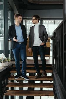 Dois homens descendo escadas conversando dentro de casa
