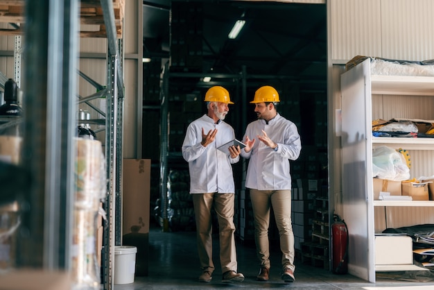 Dois homens discutindo e caminhando. interior de armazenamento. sênior segurando no tablet de mãos.