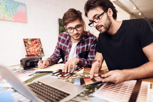 Dois homens do freelancer que olham amostras de folha da cor no portátil.