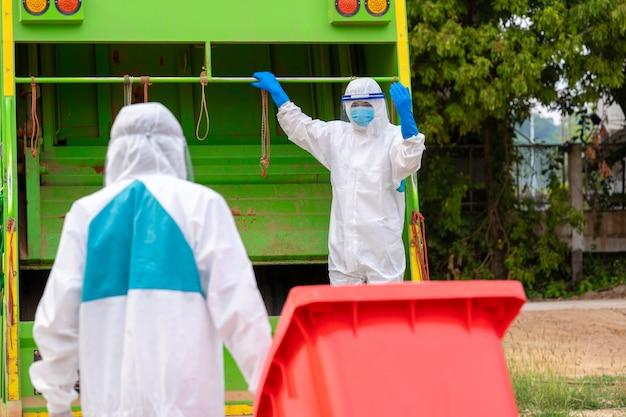 Dois homens do lixo em roupas protetoras de epi hazmat usam luvas médicas de borracha trabalhando juntas no esvaziamento de caixotes de lixo para remoção de lixo com caminhão carregando lixo e lixeira, coronavirus disease 2019.