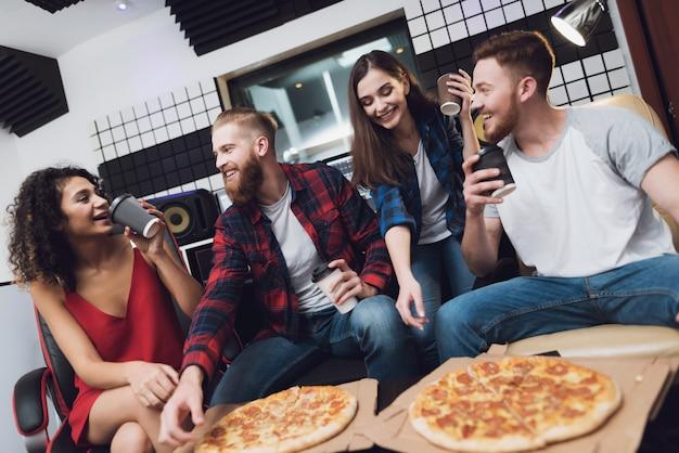 Dois homens e duas mulheres no estúdio de gravação estão comendo pizza